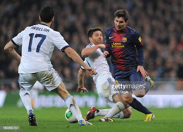 Lio Messi of FC Barcelona duels for the ball against Xabi Alonso and Ricardo Carvalho of Real Madrid CF during the Copa del Rey semi final first leg...