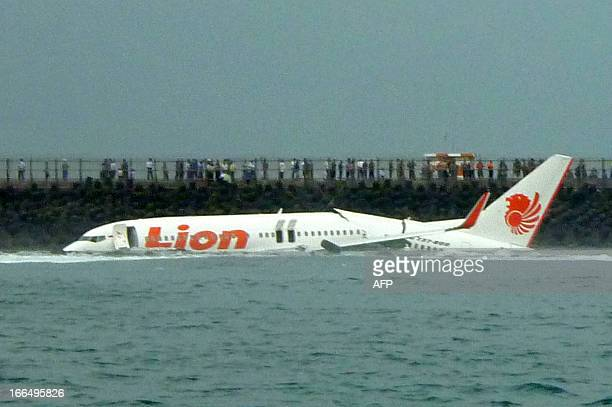 A Lion Air Boeing 737 lies submerged in the water after skidding off the runaway during landing at Bali's international airport near Denpasar on...
