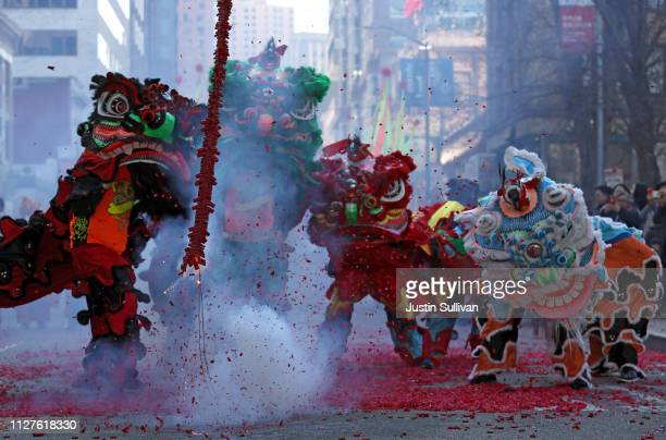 Lion dancers dance around firecrackers as they explode in the street while ushering in Chinese New Year on February 05 2019 in San Francisco...