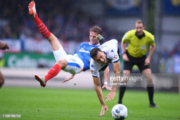 Lion Lauberbach of Holstein Kiel challenges for the ball with Lukas Froede of Karlsruher SC during the Second Bundesliga match between Holstein Kiel...