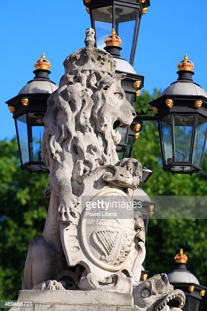 Lion sculpture and ornate lamppost at the front of Buckingham Palace