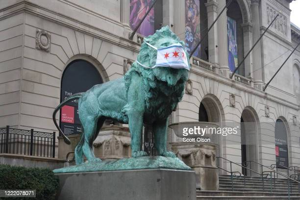 A lion sculpture in front of the Art Institute wears a mask with a depiction of the Chicago flag on April 30 2020 in Chicago Illinois On May 1 the...
