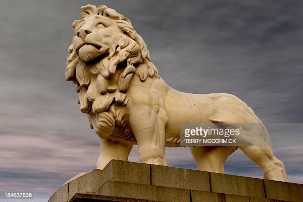 A lion statue against a cloudy sky