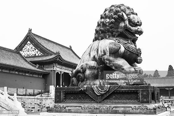 lion statue outside traditional chinese style building - pagoda stock pictures, royalty-free photos & images