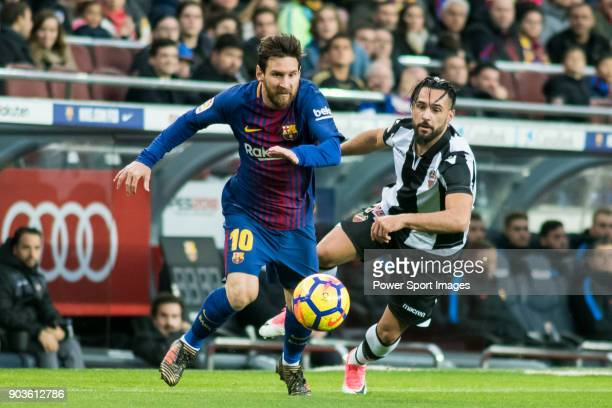 Lionel Andres Messi of FC Barcelona fights for the ball with Ivan Lopez Alvarez Ivi of Levante UD during the La Liga match between FC Barcelona and...