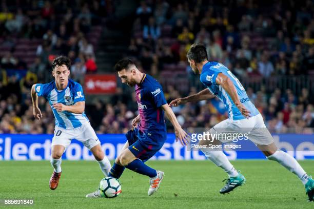 Lionel Andres Messi of FC Barcelona fights for the ball with Juan Pablo Anor Acosta Juanpi and Adrian Gonzalez Morales of Malaga CF during the La...