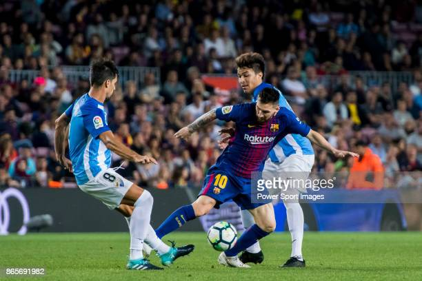 Lionel Andres Messi of FC Barcelona fights for the ball with Adalberto Penaranda of Malaga CF during the La Liga 201718 match between FC Barcelona...