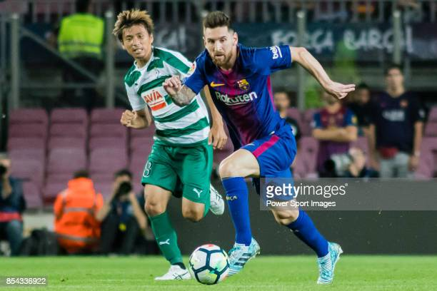 Lionel Andres Messi of FC Barcelona fights for the ball with Takashi Inui of SD Eibar during the La Liga 201718 match between FC Barcelona and SD...