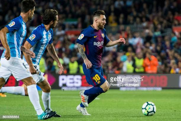 Lionel Andres Messi of FC Barcelona is followed by Paul Baysse and Adrian Gonzalez Morales of Malaga CF during the La Liga 201718 match between FC...