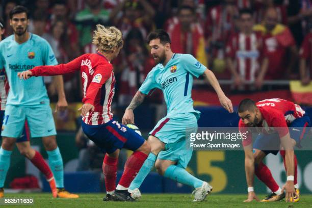 Lionel Andres Messi of FC Barcelona is tackled by Antoine Griezmann of Atletico de Madrid during the La Liga 201718 match between Atletico de Madrid...