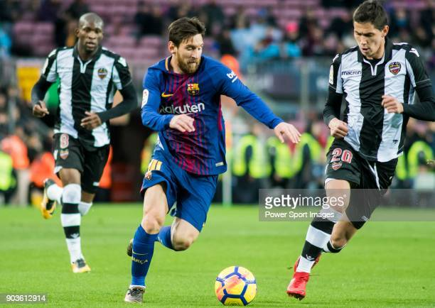 Lionel Andres Messi of FC Barcelona is tackled by Sasa Lukic of Levante UD during the La Liga match between FC Barcelona and Levante UD at Camp Nou...