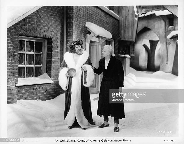 Lionel Braham leading Reginald Owen into the snow in a scene from the film 'A Christmas Carol' 1938