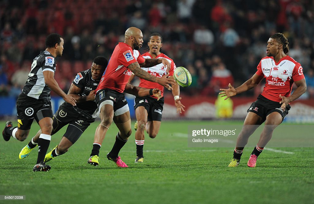Lionel Mapoe distributing the ball to Howard Mnisi of Lions with Sibusiso Sithole of Sharks tackling during the Super Rugby match between Emirates Lions and Cell C Sharks at Emirates Airline Park on July 02, 2016 in Johannesburg, South Africa.