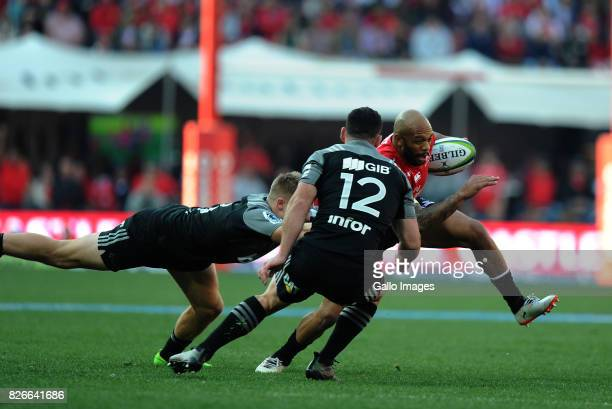 Lionel Mapoe of Lions is tackled by Jack Goodhue and Ryan Crotty of Crusaders during the Super Rugby Final match between Emirates Lions and Crusaders...