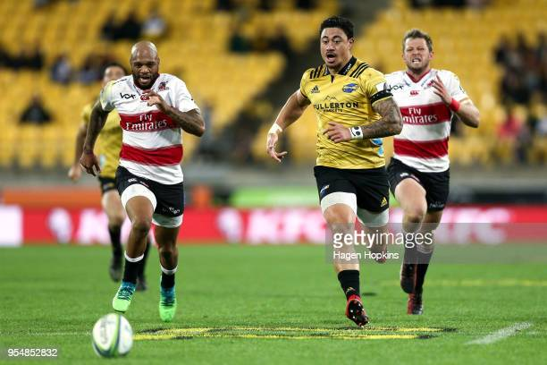 Lionel Mapoe of the Lions and Ben Lam of the Hurricanes chase a loose ball during the round 12 Super Rugby match between the Hurricanes and the Lions...
