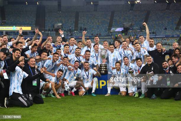 Lionel Messi and Angel Di Maria of Argentina along with teammates pose with the trophy after winning the final of Copa America Brazil 2021 between...
