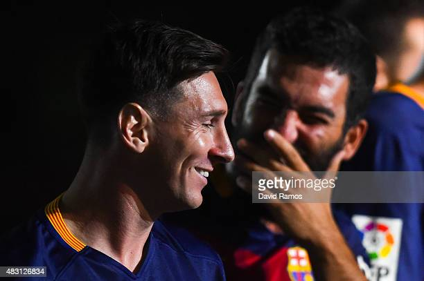 Lionel Messi and Arda Turan of FC Barcelona share a joke during the team official presentation ahead of the Joan Gamper trophy match at Camp Nou on...