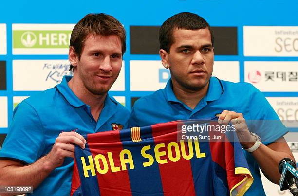 Lionel Messi and Daniel Alves of Barcelona hold a jersey during a press conference at the Mayfield hotel on August 2 2010 in Seoul South Korea FC...