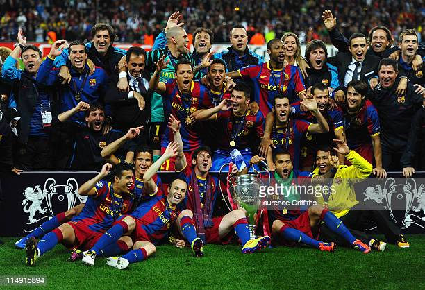 Lionel Messi and Daniel Alves of Barcelona hold the trophy as the team pose for photographs after victory in the UEFA Champions League final between...
