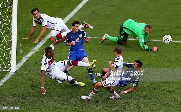 Lionel Messi and Ezequiel Lavezzi of Argentina attempt to shoot as Jerome Boateng of Germany clears the ball off the line during the 2014 FIFA World...