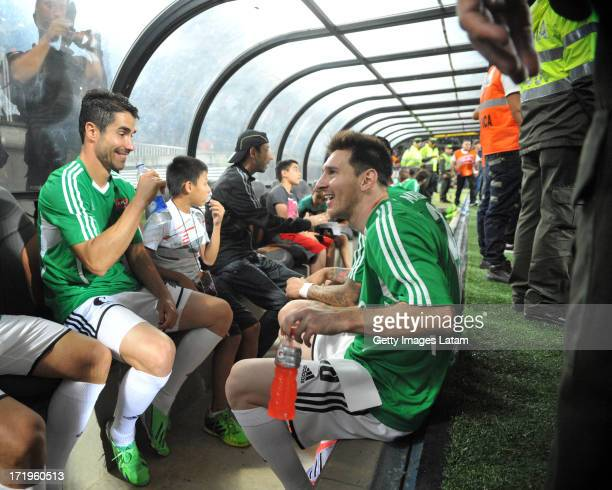 Lionel Messi and his Messi Friends teammates sit in the dugout before the start of the Messi Friends v The Rest of the World XI charity soccer match...