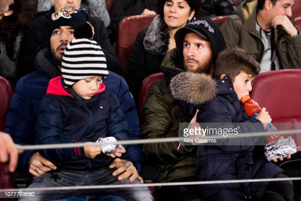 Lionel Messi and Luis Suarez of FC Barcelona sit in the stand with their sons during the Copa del Rey fourth round second leg match between FC...