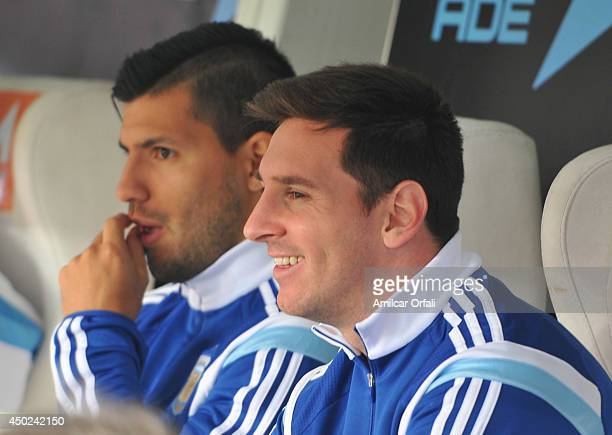Lionel Messi and Sergio Aguero of Argentina watch the game from the substitutes bench during a FIFA friendly match between Argentina and Slovenia at...
