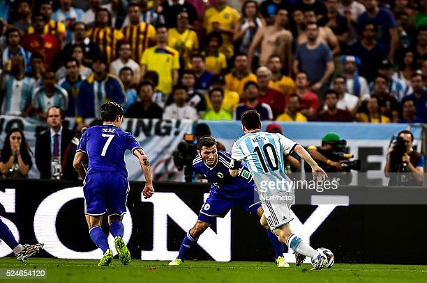 Lionel Messi attacks watched by Muhamed Besic and Sead Kolasinac at the match of the 2014 World Cup between Argentina and BosniaHerzegovina this...