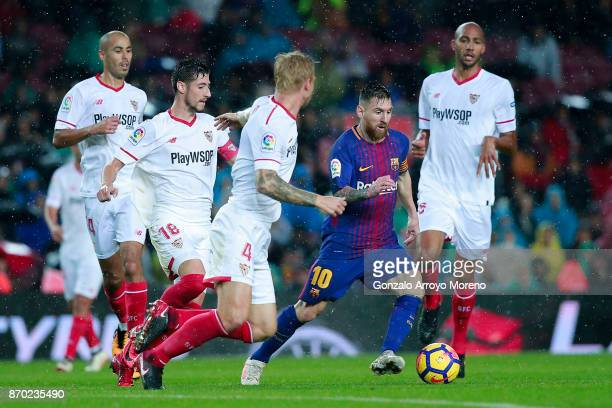Lionel Messi competes for the ball with Simon Kjaer of Sevilla FC and his team mate Steven N'Zonzi during the La Liga match between FC Barcelona and...