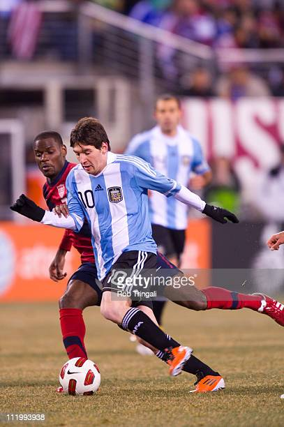 Lionel Messi forward of Argentina dribbles with the ball as Maurice Edu of the USA defends in a Soccer friendly on March 26, 2011 at the New...