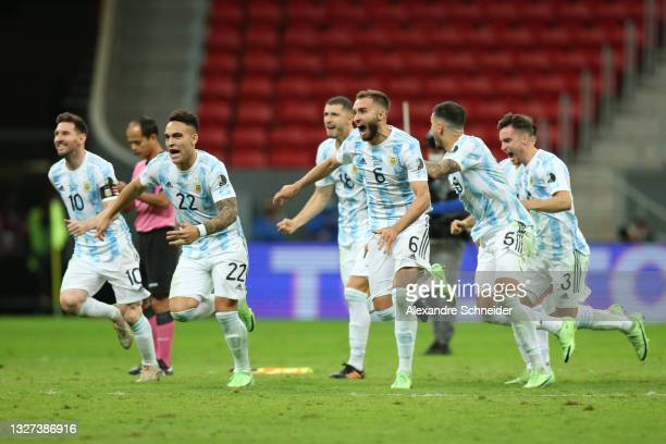 Lionel Messi, Lautaro Martinez and German Pezzella of Argentina celebrate with teammates winning a penalty shootout after a semi-final match of Copa...