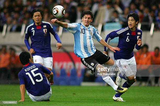 Lionel Messi of Argentina and Atsuto Uchida of Japan compete for the ball during the International Friendly match between Japan and Argentina at...