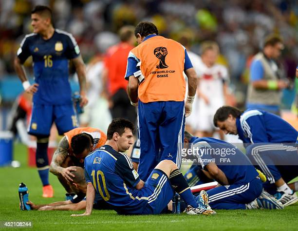 Lionel Messi of Argentina and his teammates rest on the pitch before the extra time during the 2014 FIFA World Cup Brazil Final match between Germany...