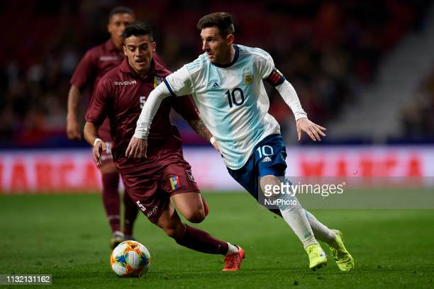 Lionel Messi of Argentina and Junior Moreno of Venezuela competes for the ball during the international friendly match between Argentina and...