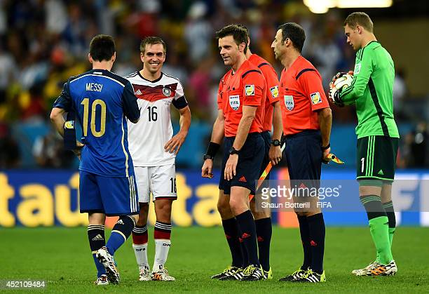 Lionel Messi of Argentina and Philipp Lahm of Germany approach to referee Nicola Rizzoli before the extra time during the 2014 FIFA World Cup Brazil...