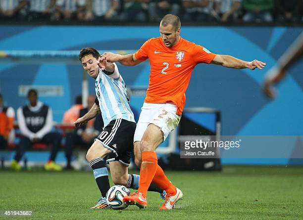 Lionel Messi of Argentina and Ron Vlaar of the Netherlands challenge for the ball during the 2014 FIFA World Cup Brazil Semi Final match between...