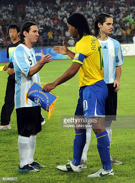 Lionel Messi of Argentina and Ronaldinho of Brazil shake hands at the start of their 2008 Beijing Olympic Games men's football semifinal match on...
