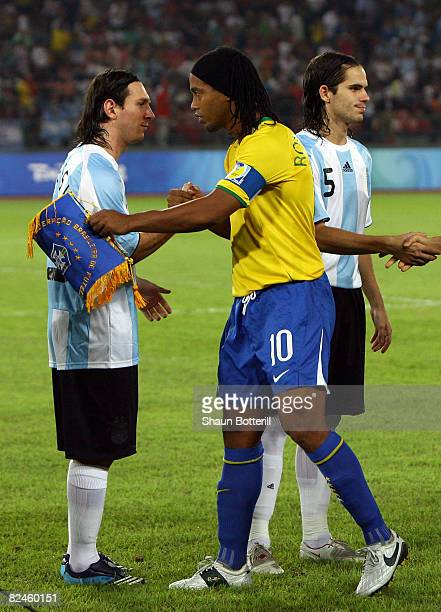 Lionel Messi of Argentina and Ronaldinho of Brazil shake hands before the men's football semifinal match between Argentina and Brazil at Workers'...