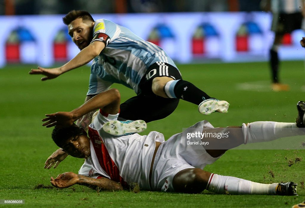 Lionel Messi of Argentina and Wilder Cartagena of Peru fall down during a match between Argentina and Peru as part of FIFA 2018 World Cup Qualifiers at Estadio Alberto J. Armando on October 5, 2017 in Buenos Aires, Argentina.