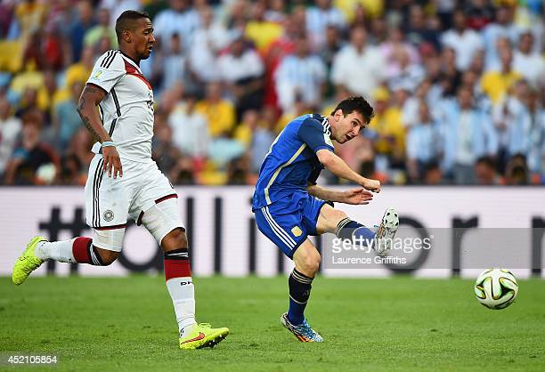 Lionel Messi of Argentina attempts a shot at goal as Jerome Boateng of Germany gives chase during the 2014 FIFA World Cup Brazil Final match between...