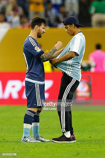 Lionel Messi of Argentina autographs the shirt of a fan who ran onto the field prior to the start of the second half during a 2016 Copa America...