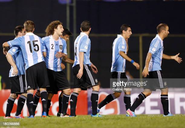 Lionel Messi of Argentina celebrates his first goal with teammates during a match between Paraguay and Argentina as part of the 16th round of the...