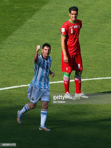 Lionel Messi of Argentina celebrates scoring his team's first goal as Reza Haghighi of Iran looks on during the 2014 FIFA World Cup Brazil Group F...