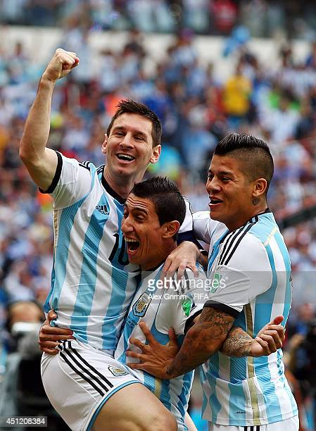 Lionel Messi of Argentina celebrates scoring his team's first goal with his teammates Angel di Maria and Marcos Rojo during the 2014 FIFA World Cup...