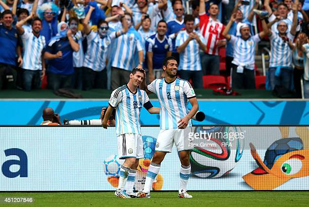 Lionel Messi of Argentina celebrates scoring his team's second goal with his teammate Ezequiel Garay during the 2014 FIFA World Cup Brazil Group F...