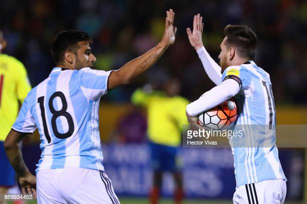 Lionel Messi of Argentina celebrates with Eduardo Salvio after scoring the first goal of his team during a match between Ecuador and Argentina as...
