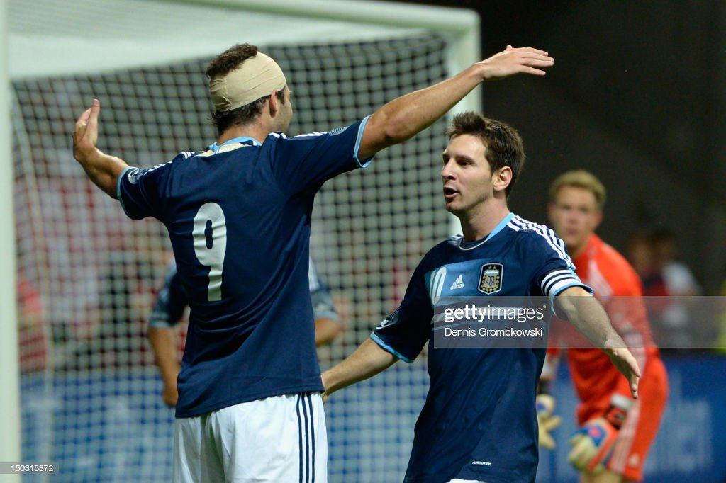 Lionel Messi of Argentina celebrates with teammate Gonzalo Higuain his team's second goal during the international friendly match between Germany and Argentina and Commerzbank-Arena on August 15, 2012 in Frankfurt am Main, Germany.