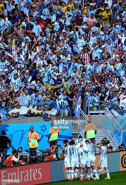 Lionel Messi of Argentina celebrates with teammates after scoring his team's first goal during the 2014 FIFA World Cup Brazil Group F match between...