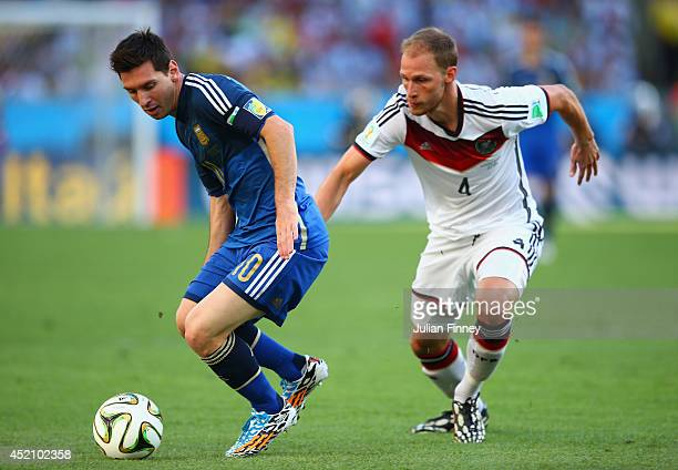 Lionel Messi of Argentina controls the ball against Benedikt Hoewedes of Germany during the 2014 FIFA World Cup Brazil Final match between Germany...