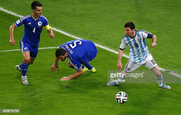 Lionel Messi of Argentina controls the ball against Emir Spahic and Sead Kolasinac of Bosnia and Herzegovina during the 2014 FIFA World Cup Brazil...